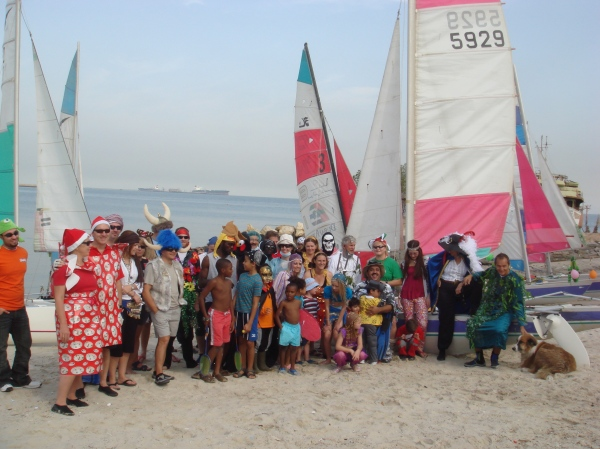 People in costume lined up in front of sailing boats