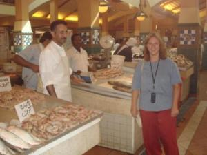 Kate stands in front of shrimp counter in market